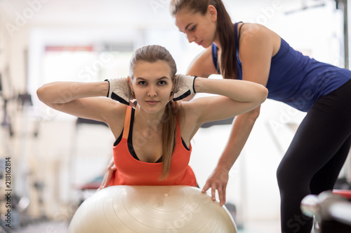 Foto op Plexiglas Fitness Fitness trainer helping young woman doing back exercises in gym