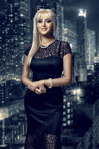Fotografie, Obraz  Retro portrait of inaccessible beautiful woman in black dress with smokey eyes and necklace stands against the background of the night city