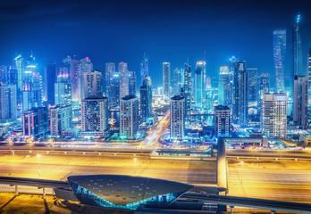 Scenic nighttime skyline of big modern city with illuminated skyscrapers. Aerial view of Dubai Marina, UAE. Multicolored travel background.