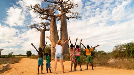 žena ushićena s crnom djecom i sjajnim drvetom baobaba, koncept afričke ujedinjenosti