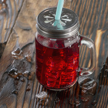 Pomegranate Juice With Ice Cubes In A Jar On A Dark Wooden Background