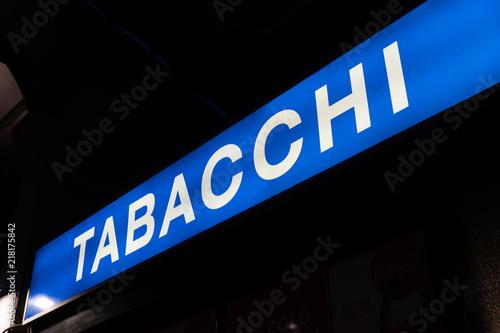 Cuadros en Lienzo Blue signage of a Tabacchi, Italian for Tobacco shop, on a black background