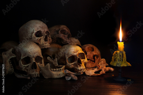 Fotografie, Obraz  Pile of skulls with bones and Candle which has flame to be bright in the dark li