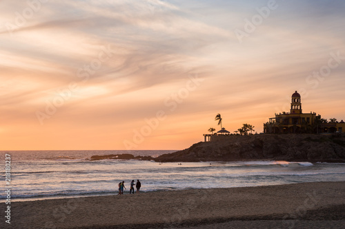 A group of friends walking on Cerritos Beach at sunset. Wallpaper Mural