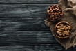 canvas print picture - almonds and hazelnuts in wooden bowls with sackcloth on dark wooden surface