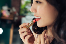 Beautiful Young Woman Applying Glossy Lipstick On Lips In Front Of A Make Up Mirror At Home