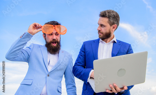 Valokuvatapetti Businessman with laptop serious while business partner ridiculous glasses looks funny