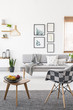 Armchair and wooden end table with fruits standing on carpet in real photo of white living room interior with posters on wall and grey lounge