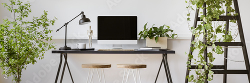 Obraz Real photo of two stools placed by home office desk with empty screen computer, lamp and coffee cup in bright room interior with fresh plants - fototapety do salonu