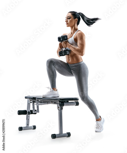 Fitness woman doing jump step ups exercise with dumbbells on bench. Photo of attractive woman in sportswear isolated on white background. Strength and motivation Wall mural
