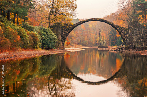 Rakotz Bridge (Rakotzbrucke, Devil's Bridge) in Kromlau, Saxony, Germany. Colorful autumn, reflection of the bridge in the water create a full circle.Unusual and interesting places in Germany.