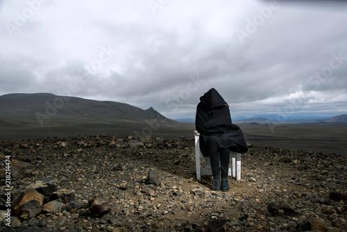 Fotografering  Reisen in Island , junge Frau sitzt in Kapuzenmantel gehüllt auf Stuhl, mit Blic