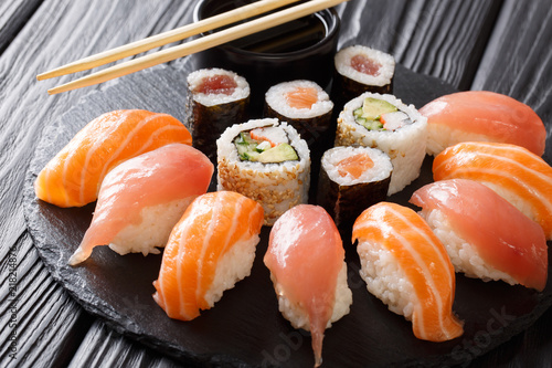 Sushi rolls set served on black stone slate on dark background