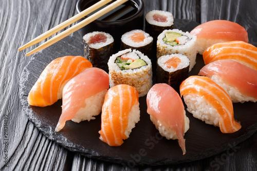 Fototapeta set of sushi and rolls with salmon and tuna, avocado, california, maki, soy sauce, chopsticks close-up. horizontal obraz