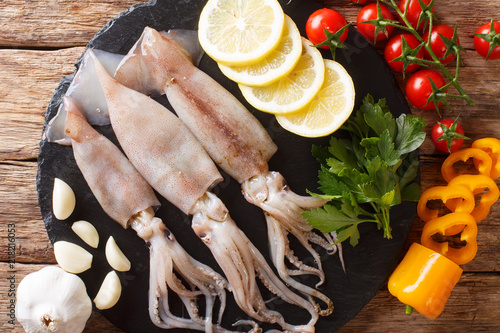Seafood fresh squid with tentacles close-up and vegetable on the table. horizontal top view from above