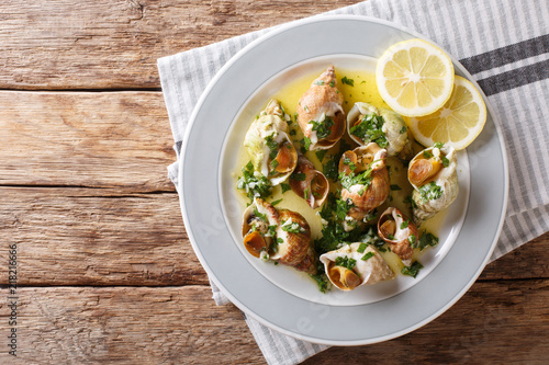 In de dag Schaaldieren French cuisine: sea snails bulot with garlic sauce and lemon close-up. horizontal top view from above