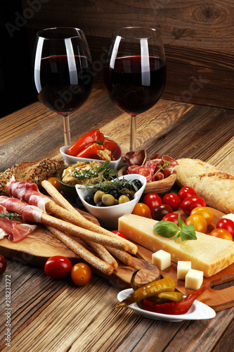 Staande foto Buffet, Bar Italian antipasti wine snacks set. Cheese variety, Mediterranean olives, crudo, Prosciutto di Parma, salami and wine in glasses over wooden grunge background.