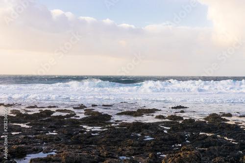 Deurstickers Canarische Eilanden Ocean waves on Lanzarote volcanic rock beach view of horizon with clouds