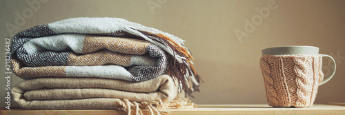 Obraz stack of beige checkered wool blankets and cup on a wooden chest. autumn - winter concept of home warmth and comfort. toned, long banner - fototapety do salonu
