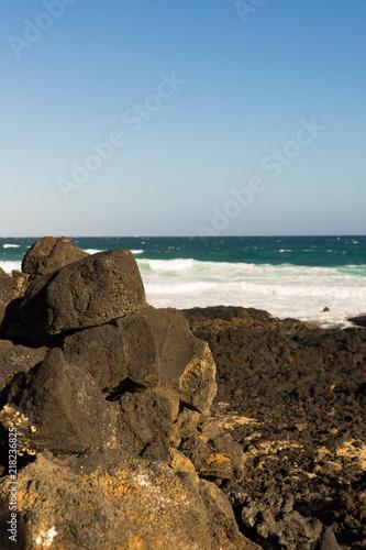Deurstickers Canarische Eilanden Black volcanic rocks stacked on Lanzarote beach with copy space