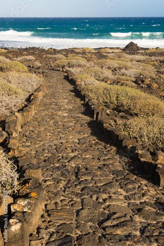 Deurstickers Canarische Eilanden Rocky path to Lanzarote beach with blue ocean waves and view of horizon