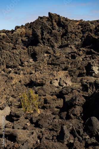 Poster Canarische Eilanden Black volcanic rock formation with blue sky on Lanzarote Island
