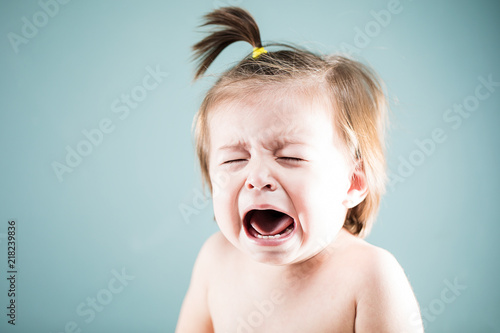 Fotografering Unhappy baby girl crying and whining