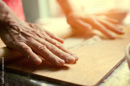 Fototapeta Woman rolls the dough with a rolling pin obraz na płótnie