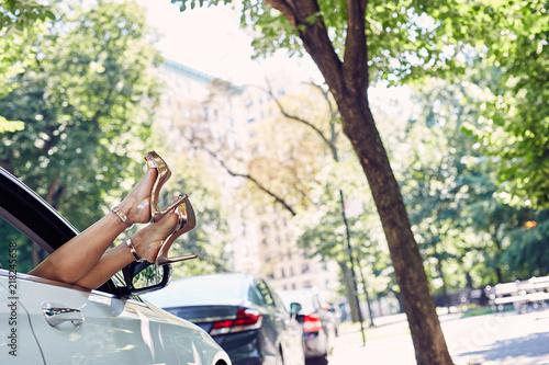 Fotografie, Obraz  High Heels Hanging outside of a luxury vehicle