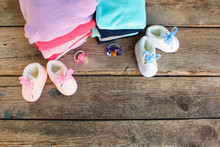 Baby Shoes, Clothing And Pacifiers Pink And Blue On The Old Wooden Background. Top View. Flat Lay.