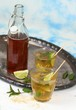 Fresh homemade lemonade with lime and mint / Drink in glasses on metal tray, brown sugar and peppermint leaves, sky background