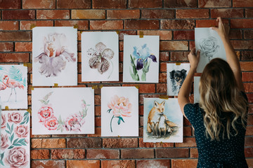 art studio workspace. painter artwork. woman sticking watercolor drawings of flowers and animals to the wall