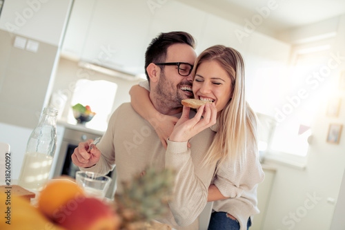 Young happy couple sitting in modern apartment and having breakfast together Fototapete