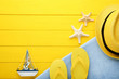 Summer accessories with decorative ship on yellow wooden table
