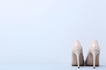 Beige high heel shoes on grey background