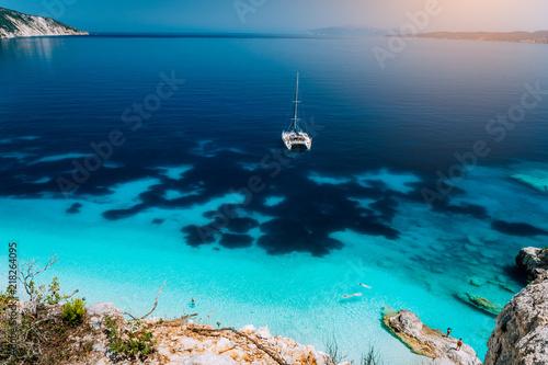 Fototapeta White catamaran yacht at anchor in calm clear azure water lagoon