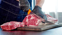 Chef Cuts Raw Meat On The Wood Board With The Knife, Close-up