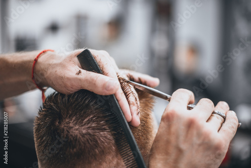 Staande foto Kapsalon Hair Care. Barber makes a haircut with scissors. Soft focus.