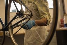 Man Repairing Bicycle Paddle Wheel In Workshop