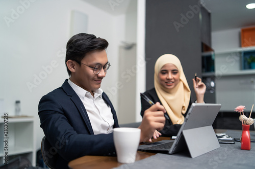 Fotografía asian malay couple working together at home with laptop and calculator