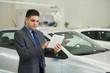 Dealer checking car properties on tablet computer