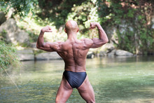 Japanese Bald Head Bodybuilder Posing The Back Double Biceps At The River