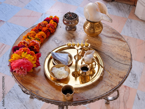Puja lamp, flower, garland, conch, incense, water, handkerchief on a copper tray - hindu worship.