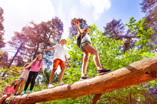 Group Of Kids Walk Over Big Log In The Forest