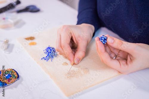 Fototapeta Professional jewelry designer making handmade eardrop with beads in studio, workshop
