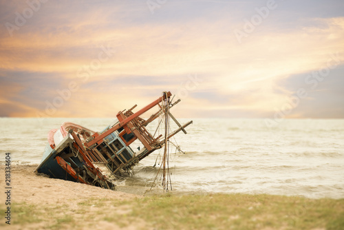 Tuinposter Schip the boat crashes at the beach background is sunset sky ,this ship was formerly a ship ,the cause of crashes is unknown, this image in fishery and logistic concept
