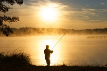 Silhouette Of Fisherman During Foggy Sunrise