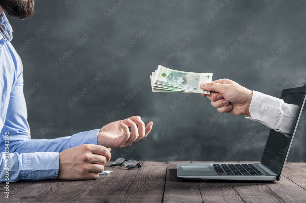 Fototapeta Businessman gets polish cash from the hand coming out of the laptop monitor. The conception of earning money on the internet