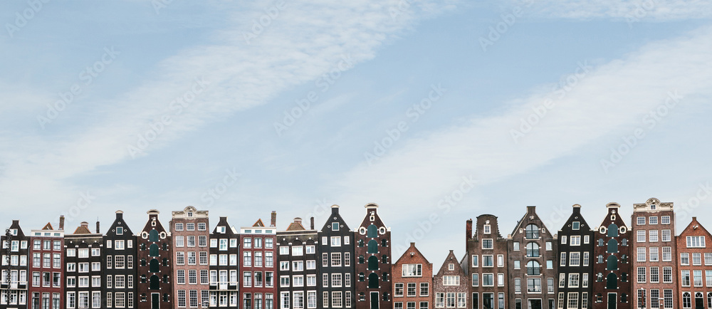Fototapeta Panorama or panoramic view. Traditional houses in Amsterdam in the Netherlands in a row against the blue sky.
