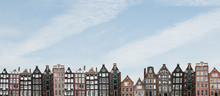 Panorama Or Panoramic View. Traditional Houses In Amsterdam In The Netherlands In A Row Against The Blue Sky.